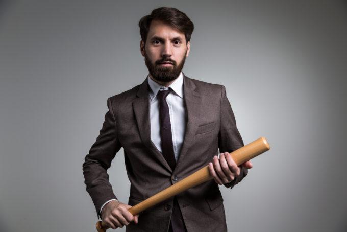 Businessman with bat symbolizing weaponized feedback